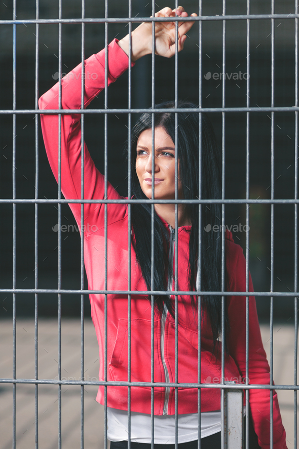 Young woman looking from behind the bars - Stock Photo - Images