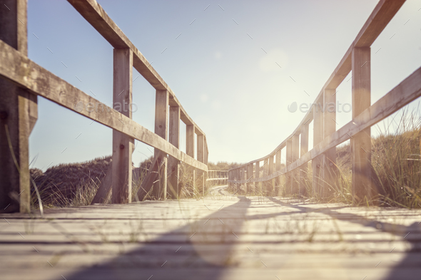 Boardwalk leading to the beach over sand dunes - Stock Photo - Images
