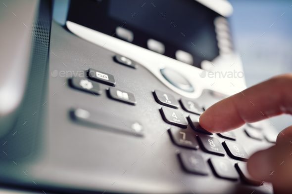 Dialing a telephone in the office - Stock Photo - Images