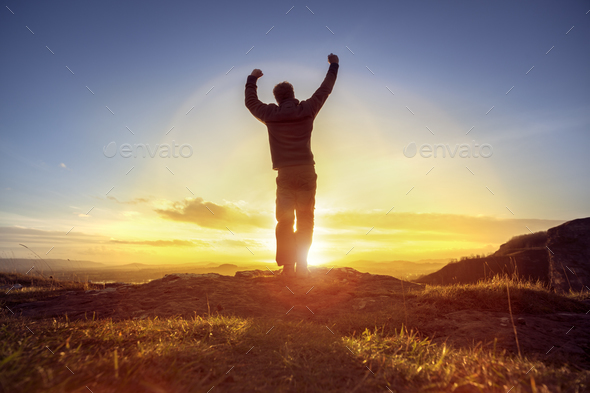 Happy man celebrating winning success against sunset - Stock Photo - Images