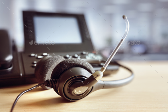 Headset headphones and telephone in call center - Stock Photo - Images