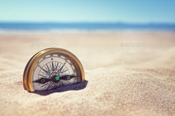 Compass on the beach with sand and sea - Stock Photo - Images