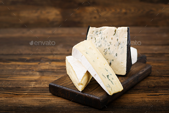 Assortment of cheeses. Camembert, dor blu, brie on a wooden background - Stock Photo - Images