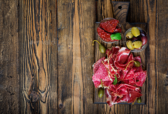 Antipasto catering platter with bacon, jerky, sausage  and olives on a wooden background. Top view - Stock Photo - Images
