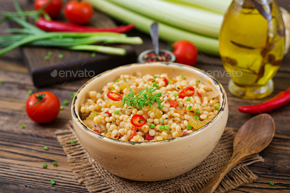 Vegetarian porridge from Turkish couscous with vegetables. Dietary menu. Vegan cuisine. - Stock Photo - Images