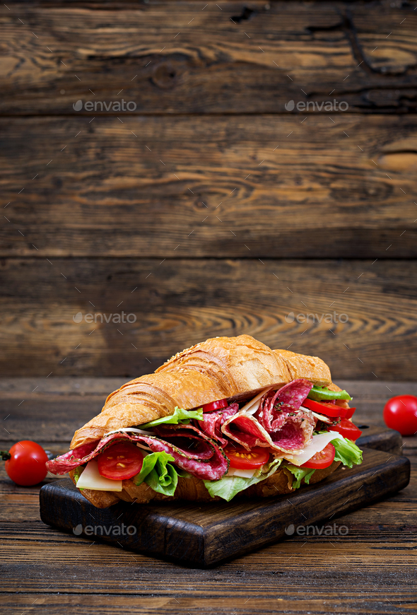 Tasty breakfast. Appetizing croissant with salami and, cheese and tomatoes - Stock Photo - Images