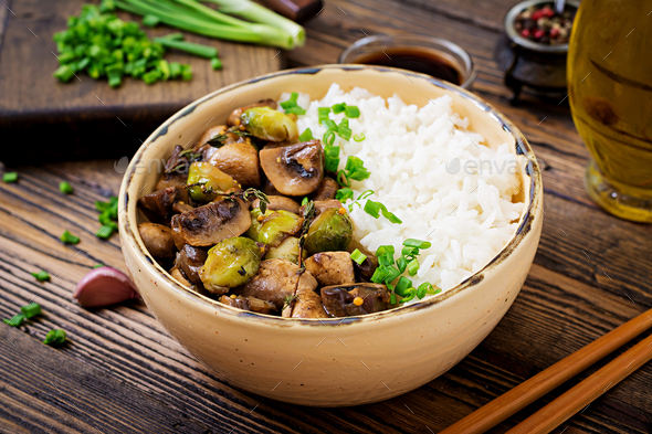 Vegan menu. Dietary food. Boiled rice with mushrooms and Brussels sprouts in Asian style. - Stock Photo - Images