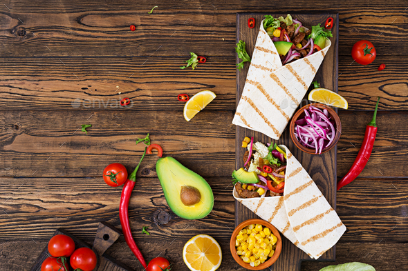 Mexican tacos with beef in tomato sauce and avocado salsa. Flat lay. Top view - Stock Photo - Images