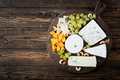 Assortment of cheeses. Camembert, dor blu, brie on a wooden background - PhotoDune Item for Sale