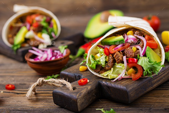 Mexican tacos with beef in tomato sauce and avocado salsa - Stock Photo - Images