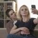Two Young, Beautiful Girls Are Sitting on the Couch and Making Selfies - VideoHive Item for Sale