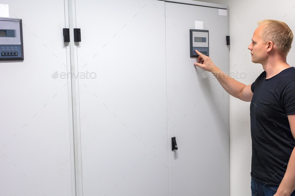 Male Technician Adjusting Air Conditioner In Datacenter - Stock Photo - Images