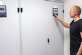 Male Technician Adjusting Air Conditioner In Datacenter - PhotoDune Item for Sale
