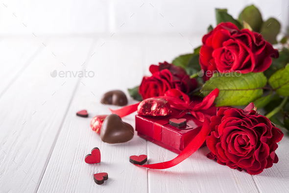 Fresh red roses and gift box on wooden table - Stock Photo - Images