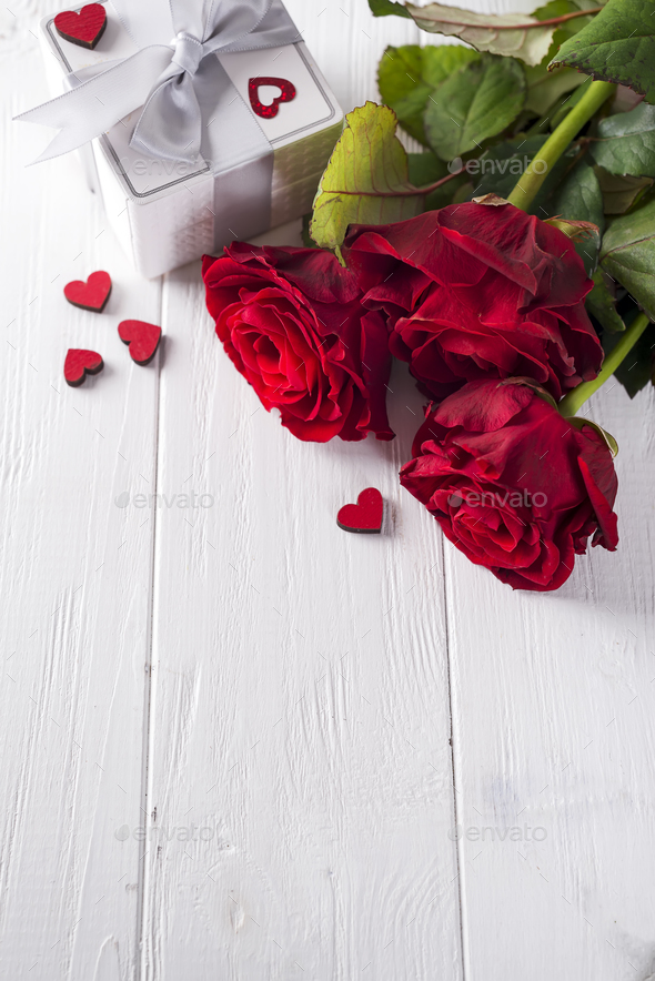 Valentines concept with bouquet of roses and wrapped gift on wooden table - Stock Photo - Images