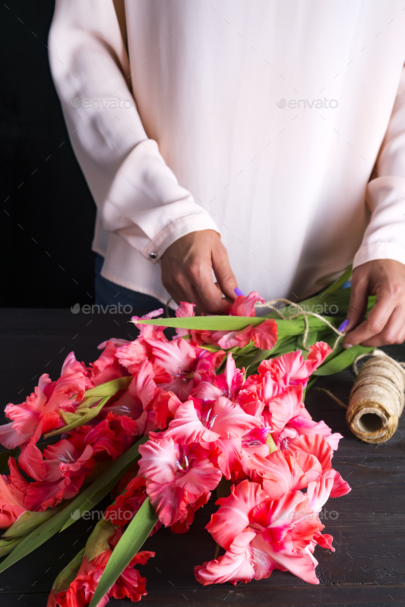 women's hands create a bouquet of flowers of gladiolus - Stock Photo - Images