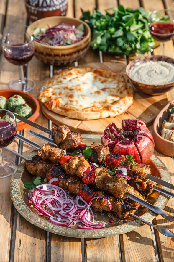 Meat shish kebab on a plate with onions, pomegranate seeds, hot pepper, wooden backdrop background - Stock Photo - Images