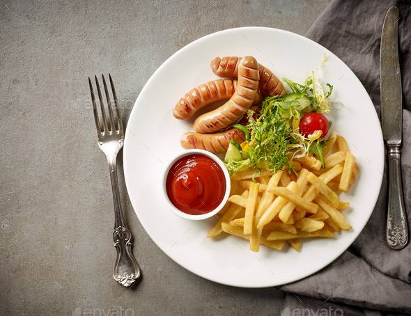 Plate of fried potatoes and sausages - Stock Photo - Images