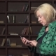 Serious Old Woman Using a Smartphone Against Bookshelf - VideoHive Item for Sale