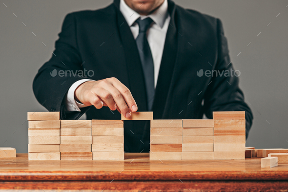 Man and wooden cubes on table. Management concept - Stock Photo - Images