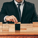 Man and wooden cubes on table. Management concept - PhotoDune Item for Sale