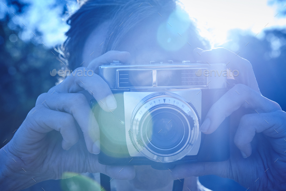 Woman taking pictures with vintage camera. Backlight. Travel background - Stock Photo - Images