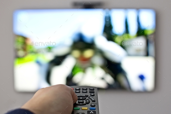 Tv and hand pressing remote control  - Stock Photo - Images
