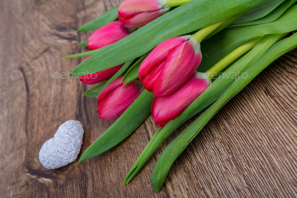 Tulips and heart on a wooden table - Stock Photo - Images