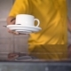 of White Coffee Cup Placed on Table By Waiter in Yellow Shirt - VideoHive Item for Sale