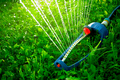 Lawn sprinkler spaying water over green grass - PhotoDune Item for Sale