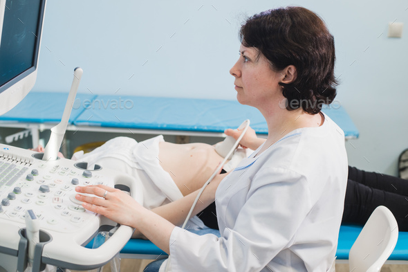 Doctor using ultrasound and screening stomach of pregnant woman. - Stock Photo - Images