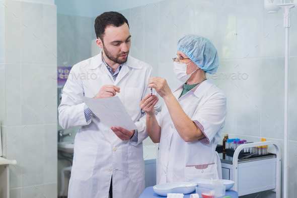Young and senior chemists working together and looking at a test tube in a clinical laboratory - Stock Photo - Images