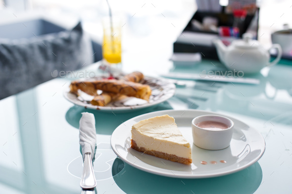 Slice of cheesecake on white plate and glass table in cafe - Stock Photo - Images