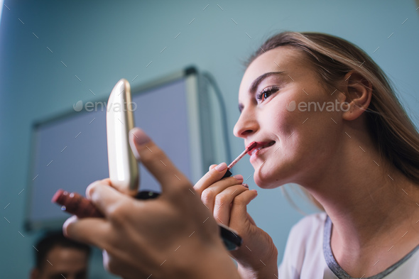 Young woman applying lipstick looking at mirror - Stock Photo - Images