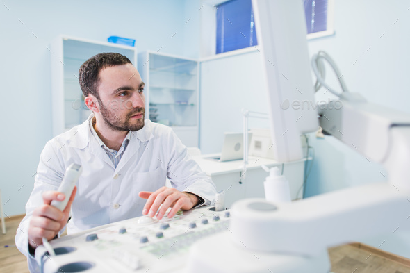 handsome doctor using an ultrasound machine - Stock Photo - Images