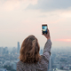 Free Download Woman taking a photo of the sunset Nulled