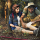 Man putting bandage on his partner knee in the jungle - PhotoDune Item for Sale