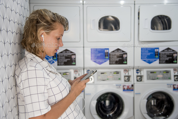Caucasian woman waiting at the self service laundryomat - Stock Photo - Images