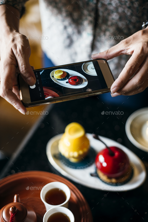 Woman taking a photo of her food - Stock Photo - Images