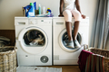 Young teen girl waiting for clothe to be washed from washing machine - PhotoDune Item for Sale