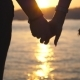 Silhouette of Male and Female Hands Holding Each Other at Sunset Against an Sea Background Young - VideoHive Item for Sale