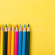 Colorful pencils on yellow background. - PhotoDune Item for Sale