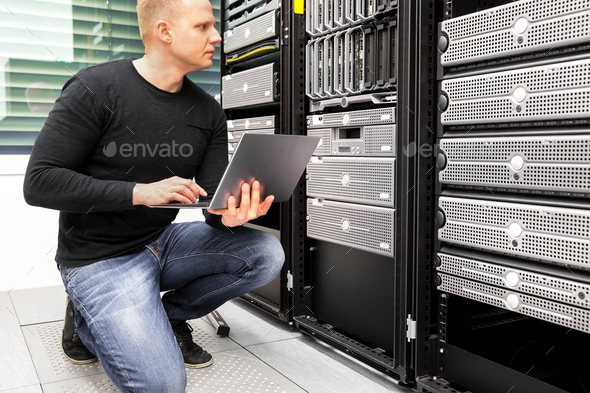 Consultant With Laptop Monitoring Servers In Datacenter - Stock Photo - Images