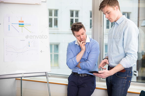 Businessmen Using Tablet Computer While Leaning On Window Sill - Stock Photo - Images