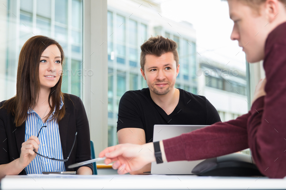 Business People Looking At Colleague Explaining At Desk - Stock Photo - Images