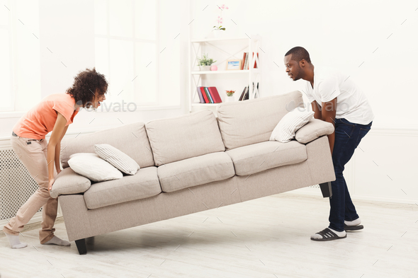 African-american couple placing sofa at new home - Stock Photo - Images