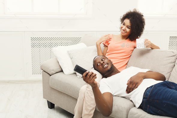 Smiling african-american young couple watching TV at home - Stock Photo - Images