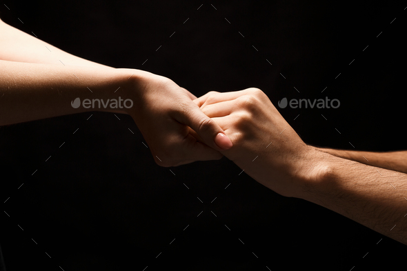 Hands of man and woman in love, isolated on black - Stock Photo - Images