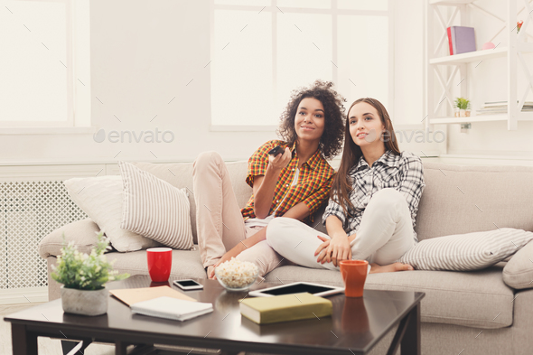Smiling female friends watching TV at home - Stock Photo - Images