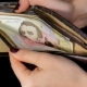 Female Hands Out Cash Dollars From Purse Dollar and Hryvnia Black Background - VideoHive Item for Sale